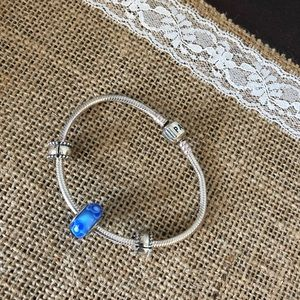 Pandora bracelet with blue glass charm.